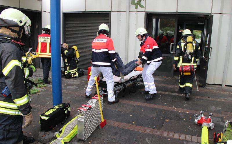 Der Rettungsdienst übernimmt den Patienten von der Feuerwehr